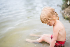 Cute toddler girl with red hair playing in water Stock Photography