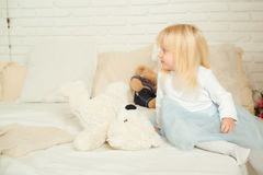 Cute toddler girl sitting on the bed with her soft toys in a light room. Happy birthday concept. Royalty Free Stock Photography