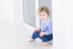 Cute toddler girl sitting at big window in living room Royalty Free Stock Images