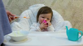 Cute toddler girl sitting in the child chair is fed porridge. With spoon by mother hand stock video