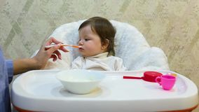 Cute toddler girl sitting in the child chair is refuses to fed porridge. With spoon by mother hand stock video