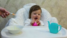 Cute toddler girl sitting in the child chair is refuses to fed porridge. With spoon by mother hand stock video footage