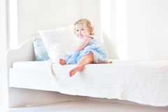 Cute toddler girl sitting on a white bed at home Royalty Free Stock Photos