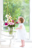 Cute toddler girl smelling fresh flowers at home Stock Photo