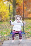 Cute toddler girl on swing with autumn trees Royalty Free Stock Photos