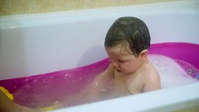 Cute toddler girl taking a bubble bath. Charming baby girl in bathroom with toy duck. close - up of mom`s hands playing with baby. Hygiene and care for toddler stock footage