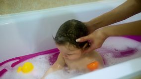 Cute toddler girl taking a bubble bath. Close-up of mom`s hands wash the baby`s head. Hygiene and care for toddler stock video