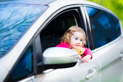 Cute toddler girl with a toy bear sitting in a car Stock Image