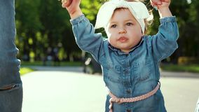 Cute toddler girl walking in sunny park with parents holding her hands stock footage