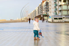 Cute toddler girl walking on winter promenade Stock Images
