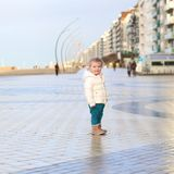 Cute toddler girl walking on winter promenade Stock Photo