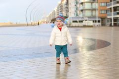 Cute toddler girl walking on winter promenade Stock Image