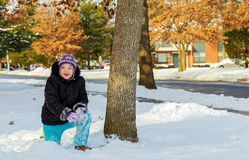 Cute toddler girl in warm snowsuit playing with a snow. Royalty Free Stock Photography