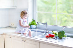 Cute toddler girl washing vegetables in kitchen sink Stock Photo
