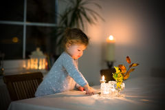 Cute toddler girl watching burning candles in dark room Royalty Free Stock Photo