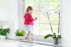 Cute toddler girl watching out window in white kitchen. Cute toddler girl in a red dress watching out a window in a beautiful white sunny kitchen with spring Stock Photography