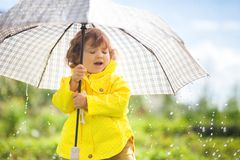 Having fun under the rain, toddler girl with umbrella. Cute toddler girl wearing yellow waterproof coat and boots with big adult umbrella having fun In the stock image