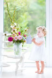 Cute toddler girl in white dress watering flowers Stock Image
