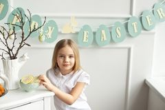 Cute toddler girl in a white shirt is eating with Easter eggs on Easter day royalty free stock image