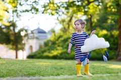 Cute toddler girl in yellow rubber boots and toy with rain drops Stock Image