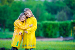 Cute toddler girls wearing waterproof coat playing outdoors by rainy and sunny day Royalty Free Stock Image