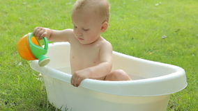 Cute toddler having a bath in garden stock video