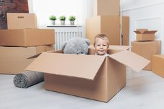 Cute toddler helping out packing boxes royalty free stock photography