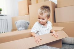 Cute toddler helping out packing boxes royalty free stock photos
