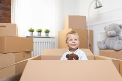Cute toddler helping out packing boxes stock images