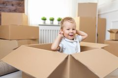 Cute toddler helping out packing boxes royalty free stock photo