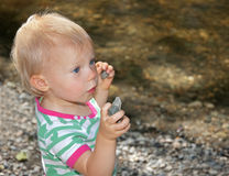 Cute Toddler Holding Rocks At Beach Stock Photo