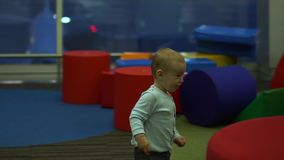 A toddler joyfully runs in the children's play area at the airport, slow motion. Cute toddler joyfully runs in the children's play area among the big colorful stock video footage