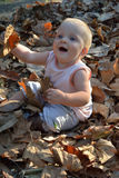 A cute toddler looking above with autumn leaves Stock Image