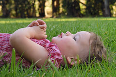 Cute Toddler Lying on the Grass. A young girl lies down in the grass and rests her hands on her chest after a long afternoon of playing at the park Royalty Free Stock Photo