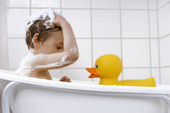 Cute toddler playing in a bathtub. Happy toddler taking a bath Stock Photo