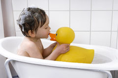Cute toddler playing in a bathtub. Little boy taking a bath with rubber duck Stock Image