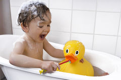 Cute toddler playing in a bathtub. Little boy taking a bath with rubber duck Stock Images