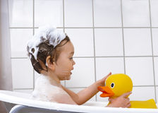 Cute toddler playing in a bathtub. Little boy taking a bath with rubber duck Royalty Free Stock Photo