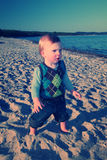Cute toddler playing on beach Stock Images