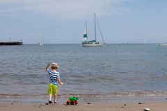 Cute toddler playing on the beach. Little boy throwing stones in the ocean Royalty Free Stock Image