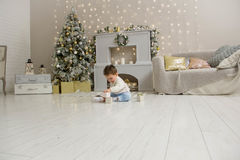 Cute toddler playing with his Christmas present in the decorated room. wooden toy. Family Xmas morning in decorated Royalty Free Stock Photos