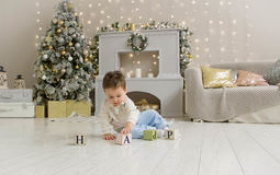 Cute toddler playing with his Christmas present in the decorated room. wooden toy. Family Xmas morning in decorated Stock Photography
