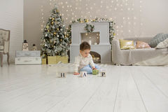 Cute toddler playing with his Christmas present in the decorated room. wooden toy. Family Xmas morning in decorated Stock Image