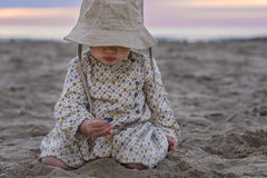 Cute toddler playing with sea shells. Cute baby girl playing with sea shells on the beach Stock Image