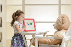 Cute toddler playing teacher role game with her toy Stock Photography