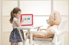 Cute toddler playing teacher role game with her toy. Happy little girl holding magnetic board with colored magnetic letters written 'love' teaching her Teddy Stock Photo