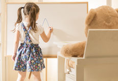 Cute toddler playing teacher role game with her toy Stock Images