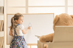 Cute toddler playing teacher role game with her toy Royalty Free Stock Images