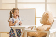 Cute toddler playing teacher role game. Little girl teaching her Teddy bear friend alphabet. Learning letters. Learn Study Education School Knowledge Concept Stock Photos