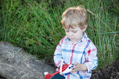 Cute toddler playing with toy in forest Stock Images